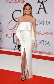 Chrissy Teigen's white Solace London strapless gown at the CFDA Fashion Awards was minimalist in design but high on feminine allure with its wavy foldover bodice and thigh-high front slit.