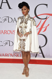 Janelle Monae cut a regal figure at the CFDA Fashion Awards in a white Tadashi Shoji cape dress lavishly ornamented with gold embroidery.