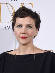 Maggie Gyllenhaal accessorized with an eye-catching pair of dangling gold chain earrings.