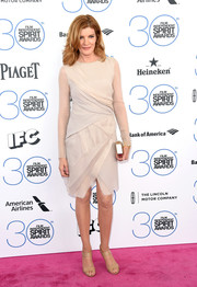 Rene Russo donned a nude cocktail dress with sheer long sleeves and crisscross layers for the Film Independent Spirit Awards.