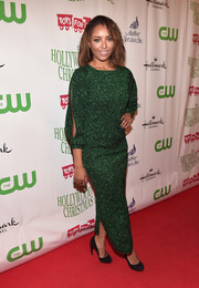Kat Graham shimmered in a sparkly emerald green dress with a side midi-slit and cut-out sleeves for a festive look.