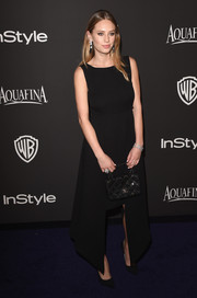 Dylan Penn opted for a simple black step-hem dress for her InStyle and Warner Bros. Golden Globes party look.