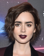 Lily Collins sealed off her vampy look with a dark burgundy lip.