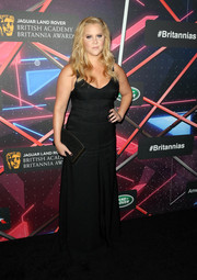 Amy Schumer put on a busty display in a low-cut black gown by Calvin Klein during the Britannia Awards.