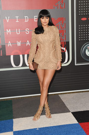 Kylie Jenner completed her monochromatic ensemble with a gold Rauwolf box clutch.