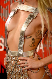 Among Miley Cyrus' many tattoos is an image of a naked woman on her left ribcage.