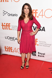 Salma Hayek dressed up her curves in a bright raspberry cocktail dress by Gucci for the TIFF premiere of 'Septembers of Shiraz.'