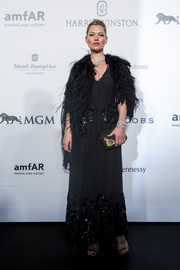 Kate Moss paired her gown with a black feather cape for added glamour.