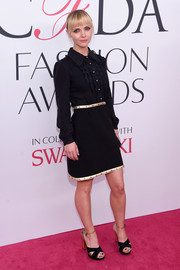 Sticking to her black and gold motif, Christina Ricci styled her dress with a pair of crisscross-strap platform sandals.