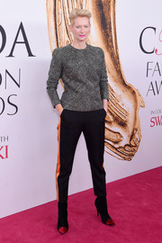 Tilda Swinton teamed her top with black and orange side-striped pants, also by Haider Ackermann.