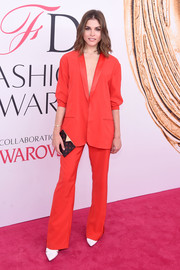 Emily Weiss paired her outfit with a Louis Vuitton printed clutch.