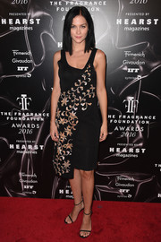 Leigh Lezark attended the 2016 Fragrance Foundation Awards wearing a sleeveless black and beige dress with floral sash-like detailing.