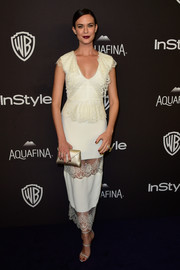 Odette Annable complemented her dress with a pair of pale gray triple-strap sandals.
