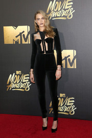 Cara Delevingne kept up the sexy vibe with a pair of tight black pants, also by Balmain.