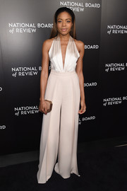 Naomi Harris styled her look with a tan satin clutch by Amanda Pearl.
