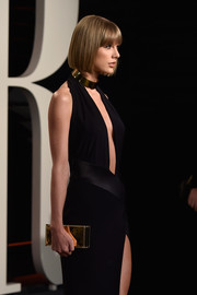 Taylor Swift teamed a Jimmy Choo mirrored box clutch with a plunging black halter dress for an ultra-modern look during the Vanity Fair Oscar party.