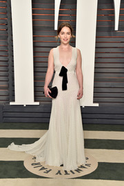 Emilia Clarke donned a cute and sexy Miu Miu pin-dot gown with a bow-adorned, plunging neckline for the Vanity Fair Oscar party.