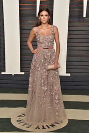 Nina Dobrev paired her dress with a beige tube clutch by Amanda Pearl.