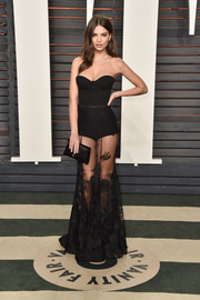 Emily Ratajkowski complemented her dress with a black satin envelope clutch by Tyler Alexandra.