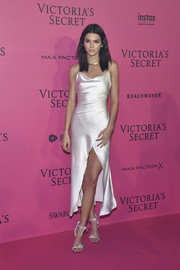 Kendall Jenner complemented her dress with white knot-detail sandals by Atelier Versace.