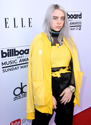 Billie Eilish accessorized with a stylish gold chronograph watch.