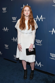 Sadie Sink topped off her ensemble with a black suede clutch.