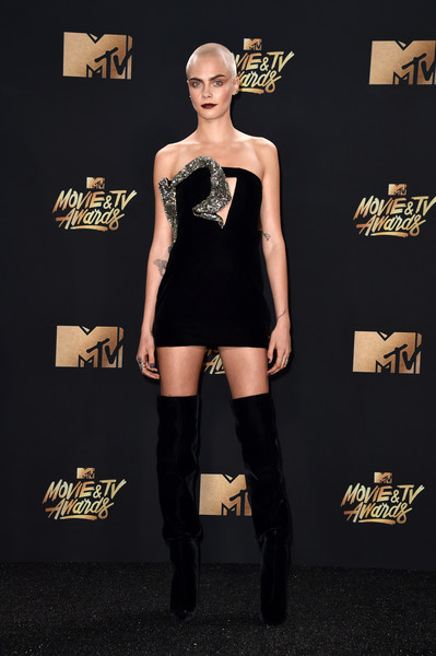 Cara Delevingne sealed off her edgy look with black velvet thigh-high boots, also by Saint Laurent.
