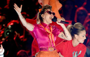 Miley Cyrus completed her colorful outfit with an orange silk scarf.