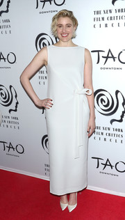 Greta Gerwig matched her dress with a pair of white satin pumps.