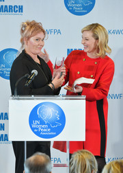 Cate Blanchett was classic in a red wool coat with gold buttons and black side stripes at the UN Women for Peace Association luncheon.