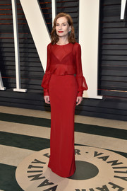Isabelle Huppert looked perfectly polished in a sheer-bodice red gown by Armani Prive at the Vanity Fair Oscar party.