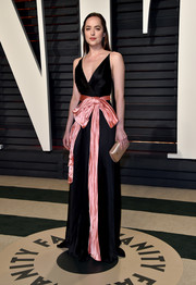 Dakota Johnson looked fetching in a black Gucci wrap gown with a pink bow belt at the Vanity Fair Oscar party.