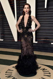 Lily Collins flashed some skin in a sheer, deep-V black gown by Elie Saab Couture at the Vanity Fair Oscar party.