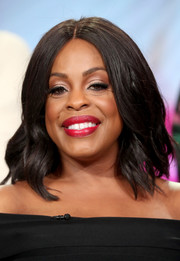 Niecy Nashy attended the 2017 Winter TCA Tour wearing this center-parted, mid-length wavy 'do.