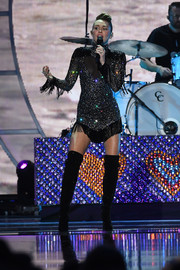 Miley Cyrus complemented her dress with black over-the-knee boots.