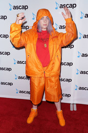Billie Eilish complemented her outfit with a pair of orange high-top sneakers.