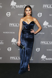 Olivia Culpo teamed her dress with a shiny black clutch by Edie Parker.