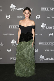 Rachel Bilson got glam in a Johanna Ortiz off-the-shoulder gown with a feather-festooned skirt and oversized floral detailing for the 2018 Baby2Baby Gala.