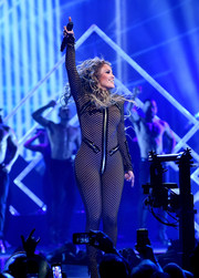 Jennifer Lopez flaunted her flawless figure in a black fishnet catsuit while performing at the 2018 DirecTV Now Super Saturday Night concert.