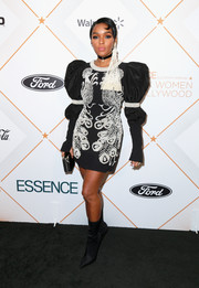 Janelle Monae teamed her dress with black satin mid-calf boots by Steve Madden.