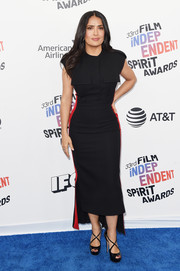 Salma Hayek cut a curvy silhouette in a black Alexander McQueen midi dress with red side stripes and military pockets at the 2018 Film Independent Spirit Awards.