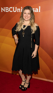 Kelly Clarkson oozed feminine appeal wearing this scalloped off-the-shoulder dress by Alexander McQueen at the 2018 NBCUniversal Winter Press Tour.