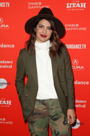 Priyanka Chopra kept cozy in a white turtleneck layered under an olive-green blazer at the Sundance premiere of 'Burden the Park.'