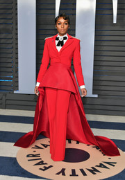 Janelle Monae commanded attention in a red Christian Siriano pantsuit with a long train at the 2018 Vanity Fair Oscar party.