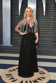 Molly Sims turned heads in a semi-sheer black Zuhair Murad gown with a matching embellished capelet at the 2018 Vanity Fair Oscar party.
