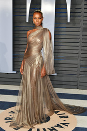 Jasmine Tookes looked ethereal in a sheer, asymmetrical gold gown by Jean-Louis Sabaji at the 2018 Vanity Fair Oscar party.