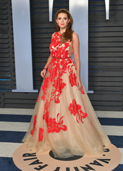 Carly Steel attended the 2018 Vanity Fair Oscar party wearing a nude tulle gown with red floral embroidery.