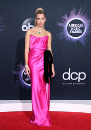Dua Lipa looked ultra feminine in a strapless hot-pink column dress with black velvet bow detailing at the 2019 American Music Awards.