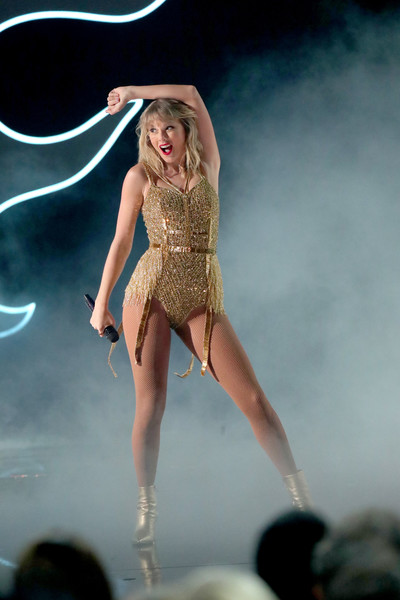 Taylor Swift looked flirty in a beaded and fringed gold bodysuit while performing at the 2019 American Music Awards.