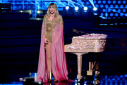Taylor Swift layered an embellished pink cape over a gold bodysuit for her performance at the 2019 American Music Awards.
